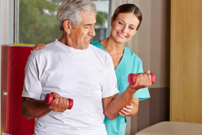 senior man with dumbbells in rehab center with caregiver