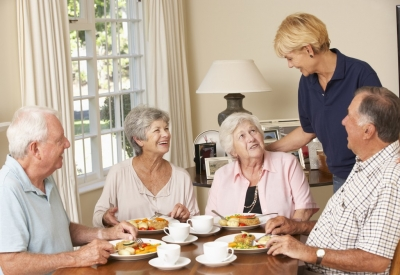 group of senior couples enjoying meal together at home with caregiver tending to their needs
