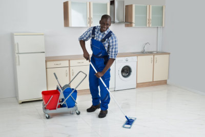 happy adult man mopping the floor
