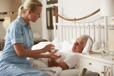 nurse giving elder man medicine on bed