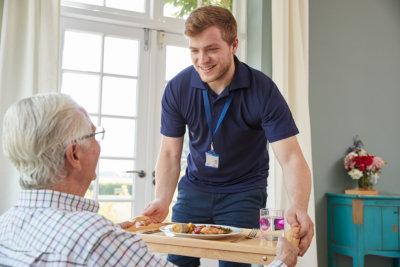 adult caregiver serving dinner to a senior man