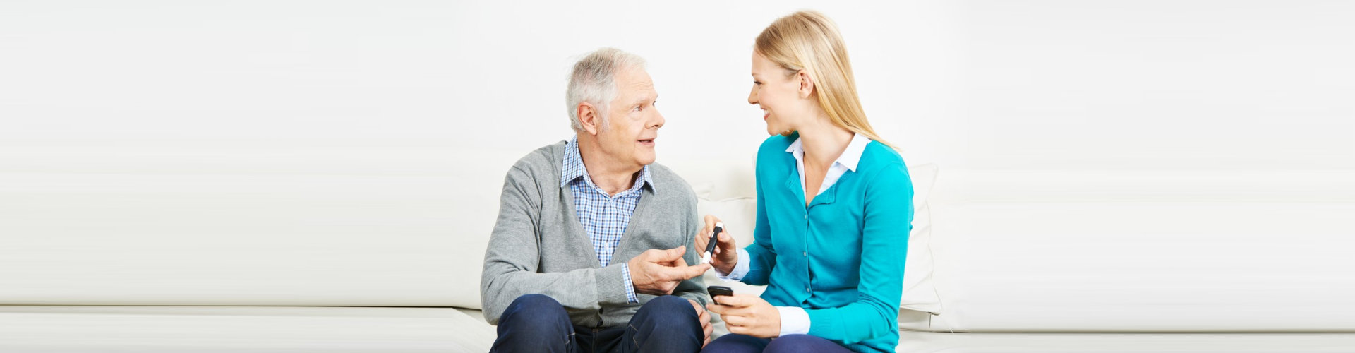 nurse taking elder man's blood sugar level using a glucometer