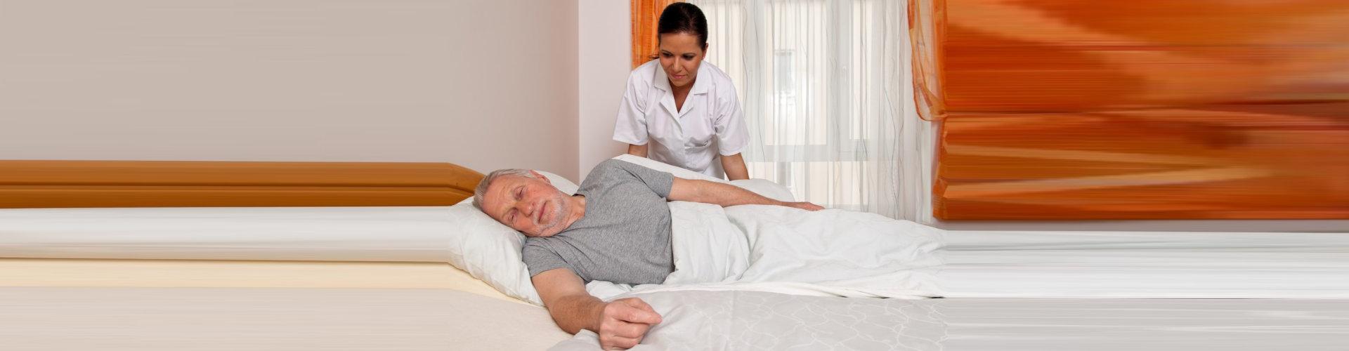 caregiver assisting elder man on bed